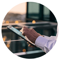 Business man holding tablet device outside at sunset