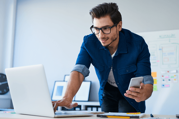 Man using laptop and cell phone for site discovery in modern workforce