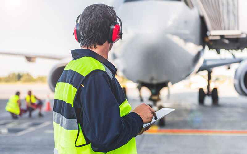 Aircraft engineer uses tablet in front of airplane