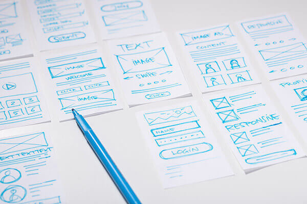Wireframes of multiple application designs displayed on table