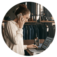 Small business owner on phone and laptop in clothing store