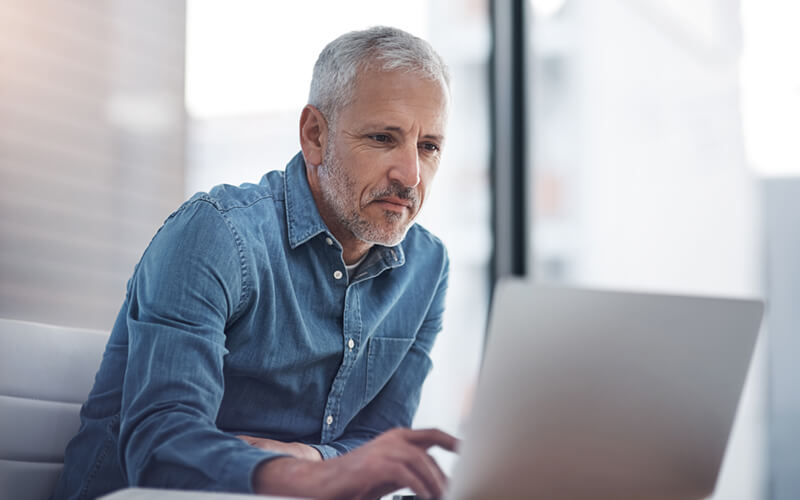 Mature businessman uses software asset management tools on laptop