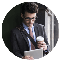 Business man on tablet holding cup of coffee.