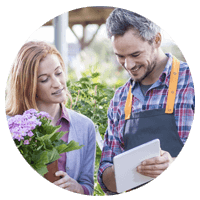 Retail flower shop employee using tablet computer to look-up inventory with client