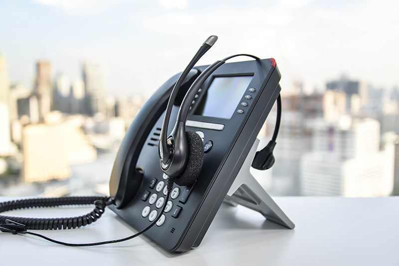 VoIP phone with headset isolated on office desk