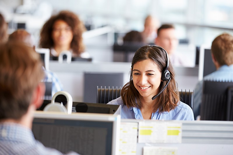 Young woman working in call center, surrounded by colleagues