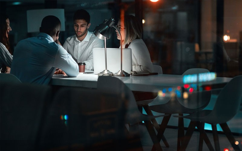 Group of employees working in office at night