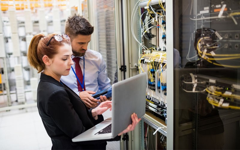 Two professionals working in network server room