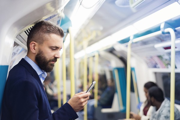 Businessman reading article on iPhone while on the subway